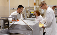 Hui Wang, CCUR pilot plant manager, (left) assists students with blanching vegetables.