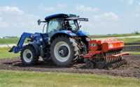 Image of a blue tractor planting switchgrass in a field.